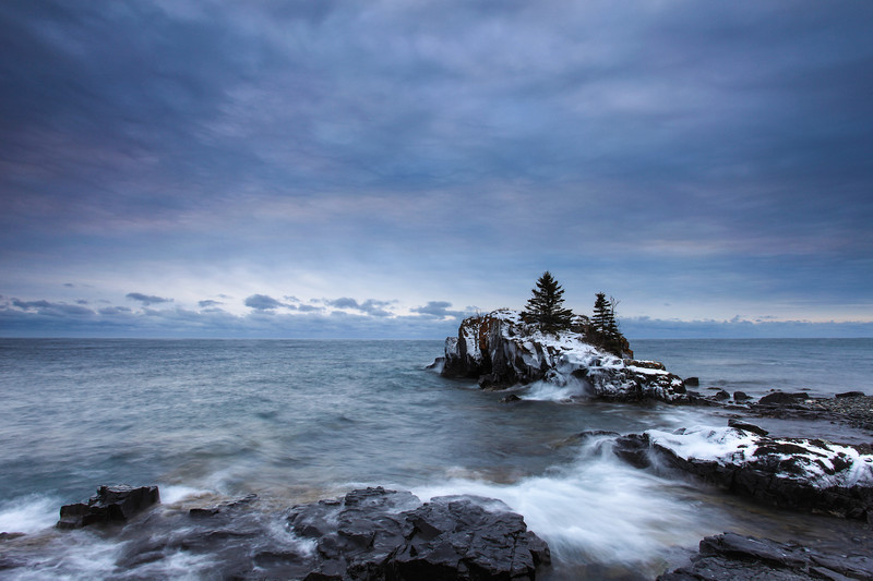 "THURSDAY, NOVEMBER 29, 2012<br /> <br /> SUPERIOR WINTER 8262<br /> <br /> ""Cloudy November morning at Hollow Rock""<br /> <br /> I went out this morning to try and catch a Lake Superior sunrise for the first time in a LONG time.  As I drove to my chosen location the clouds started to light up with color as the sun approached the horizon. Less than 5 minutes later, however, that brief splash of color was gone.  I waited an hour for some more amazing light to appear, but it was not meant to be on this morning.  I still shot several images, and this one was my favorite.  While not the most impressive in terms of color, there is a lot of very subtle variation in color going on.  Plus, the waves made for a nice touch as they broke upon the shore.   <br /> <br /> Camera: Canon EOS 5D Mark II<br /> Lens: Canon EF 17-40mm<br /> Focal length: 17mm<br /> Shutter speed: 1.3 seconds<br /> Aperture: f/16<br /> ISO: 50"