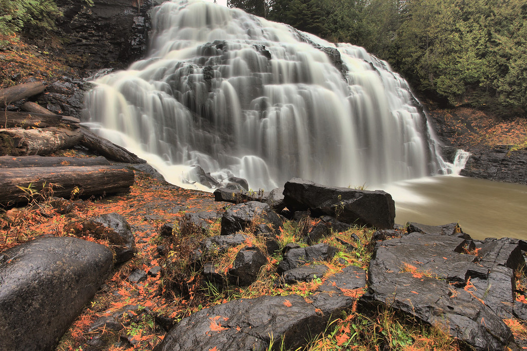 """THURSDAY, OCTOBER 18, 2012<br /> <br /> PIGEON RIVER 7701<br /> <br /> """"Autumn at Partridge Falls""""<br /> <br /> Yesterday we went up to Partridge Falls, one of my favorite places to visit although only the second time this year I've been there. I've been wanting to make it there for a while, since the river is pretty low and I find the waterfall more fascinating and beautiful when the water is low than when it is high. No matter what the water level, Partridge Falls never disappoints. Thanks to some recent winds the rocks at the base of the falls were littered with sheds from nearby cedar trees. I wanted to show the color from the fallen cedar, so I chose a composition that showed more foreground than I usually show when photographing the falls. Because of the high contrast between the very dark rocks in the foreground and the brightness of the waterfall, I had to shoot 3 images at different exposure settings then blend them together using photo software in order to show the complete range of light in the scene.<br /> <br /> Camera: Canon EOS 5D Mark II<br /> Lens: Canon EF 17-40mm<br /> Focal length: 17mm<br /> Shutter speed: 2.5 seconds<br /> Aperture: f/22<br /> ISO: 50"""