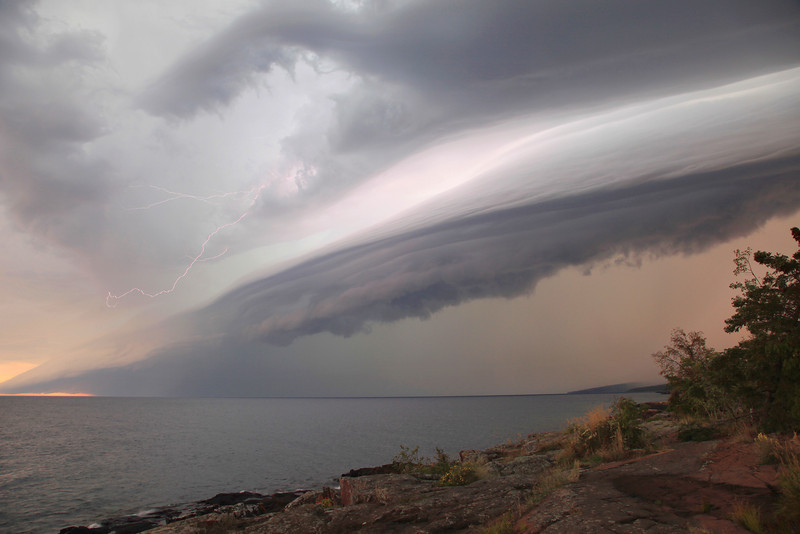 """SATURDAY, SEPTEMBER 8, 2012<br /> <br /> LIGHTNING 5169<br /> <br /> """"September Storm over Lake Superior""""<br /> <br /> After our hike we headed in to Grand Marais and when we arrived in town the weather was absolutely perfect for a late summer/early fall day. Virtually no wind, sunny sky and lots of """"popcorn"""" clouds. A couple of hours later a storm front moved in from the west and before we knew it the sky was dominated by this huge wall cloud that was rolling in overhead. Lightning flashed every few seconds as the storm approached. There was an eerie calm that preceeded the storm, but once the """"wall"""" was over us, the wind hit shortly after and then the rain came. It poured for about half an hour, the wind blew and the lightning flashed. As we drove back home we were following the storm and were treated to a nice display of lightning ahead of us while a rainbow floated out over the lake to our right. By the time the sun went down everything was calm again.<br /> <br /> Camera: Canon EOS 5D Mark II<br /> Lens: Canon EF 24-105mm<br /> Focal length: 24mm<br /> Shutter speed: 1/4 second<br /> Aperture: f/8<br /> ISO: 200"""