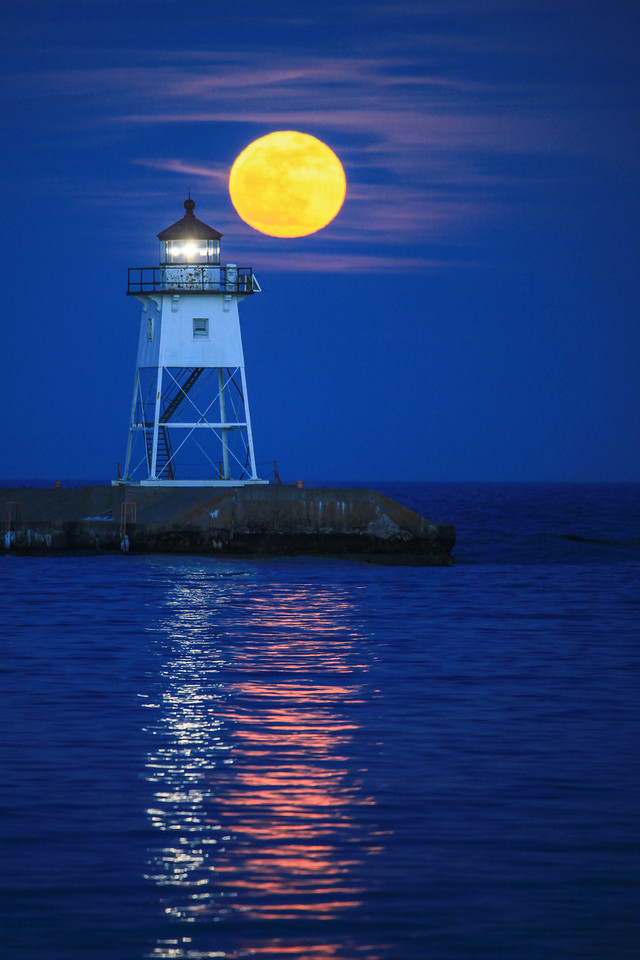 "THURSDAY, APRIL 25, 2013<br /> <br /> SUPERIOR SPRING 2215<br /> <br /> ""April moonrise over the Grand Marais Lighthouse""<br /> <br /> Last night after work we headed to Grand Marais to photograph the rising full moon behind the lighthouse.  At first it looked as though we may not see the moon much if at all, because there was what appeared to be a cloud bank forming on the eastern horizon.  As it turned out, though, we were able to see the moon completely and once it rose a little ways into the sky the thin clouds started to illuminate from the moonlight and really complemented the scene.  I made plenty of photos as the moon passed behind the lighthouse, but this one where the moon is just above and to the right of the lighthouse is my favorite.  I really liked how the reflection of the moonlight and the reflection of the lighthouse light are side by side on the water.  What a magical sight!<br /> <br /> Camera: Canon EOS 5D Mark II<br /> Lens: Canon EF 100-400mm<br /> Focal length: 400mm<br /> Shutter speed: 1/6 sec<br /> Aperture: f/5.6<br /> ISO: 800"