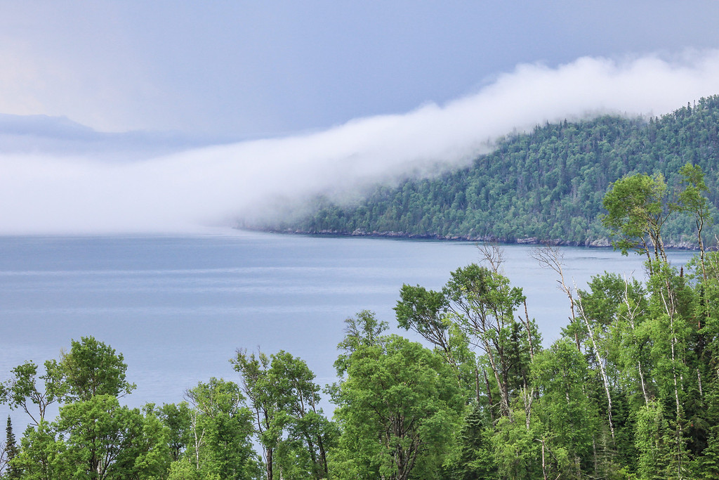 "SATURDAY, AUGUST 31, 2013<br /> <br /> SUPERIOR SUMMER 4536<br /> <br /> ""The Summer of Fog""<br /> <br /> We sure have had a lot of fog this summer!  Thanks to the cooler temps overall this year, Lake Superior has not warmed up as much as it normally would and that means that we've had quite a bit of fog.  When we have had warm days, the warm air mass coming from land clashes with the cooler air mass over the lake and creates fog.  It seems we've had more foggy days than not this year.  In honor of that phenomenon, I'm sharing this photo from earlier this summer.  This photo was taken on June 27th of this year and shows a blanket of fog rolling over the top of Hat Point in Grand Portage.  <br /> <br /> Camera: Canon EOS 5D Mark II<br /> Lens: Canon EF 100-400mm<br /> Focal length: 180mm<br /> Shutter speed: 1/160<br /> Aperture: f/16<br /> ISO: 800"