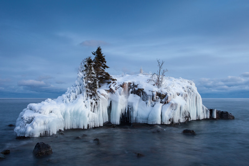 "FRIDAY, DECEMBER 13, 2013<br /> <br /> SUPERIOR WINTER 8973<br /> <br /> ""Covered in Ice""<br /> <br /> What a difference a year can make in the appearance of a subject.  At this time last year I was photographing Hollow Rock (it is one of my favorite things to photograph in December) and there was almost ZERO ice on the rock.  This year, the rock is pretty much completely covered in ice.  This is largely due to a major winter storm that we had just over a week ago.  During the storm the rock was pummeled by large waves rolling in from the east.  When the waves collided with the rock, spray went flying up and over the top of the rock.  The air was cold enough that a lot of the spray froze when it made contact with the rock.  What you see here is the result of big waves and cold air temperatures.  I don't think I've ever seen the rock covered with so much ice so early in the winter.  This is shaping up to be an excellent year for ice photography on the big lake.  I can't wait to see what the rest of the winter will bring!<br /> <br /> Camera: Canon EOS 5D Mark II<br /> Lens: Canon EF 17-40mm<br /> Focal length: 32mm<br /> Shutter speed: 2.5 seconds<br /> Aperture: f/16<br /> ISO: 100"