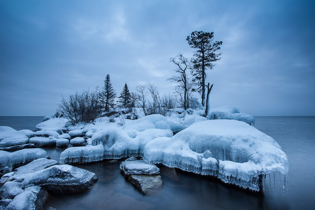 """SATURDAY, DECEMBER 21, 2013<br /> <br /> SUPERIOR WINTER 9100<br /> <br /> """"Island of Ice""""<br /> <br /> This morning I explored a piece of Lake Superior shoreline that had some really beautiful ice formations.  Even though it was cloudy and snowing, there were a few breaks in the clouds and I was hopeful for an amazing sunrise filled with color.  That didn't happen, but I still enjoyed my time on the shore.  Even though there was not much color, the scene was still extraordinary.  The ice formations were sublime.  I loved the """"skirt"""" of ice that lined the rocks surrounding the island.  The morning was extremely quiet with only the slightest breeze and I swear I could actually hear the snow hitting the ground as it fell.  Peaceful mornings along the Lake Superior shoreline are the best, and this one certainly qualified!<br /> <br /> Camera: Canon EOS 5D Mark II<br /> Lens: Canon EF 17-40mm<br /> Focal length: 17mm<br /> Shutter speed: 4 seconds<br /> Aperture: f/16<br /> ISO: 50"""