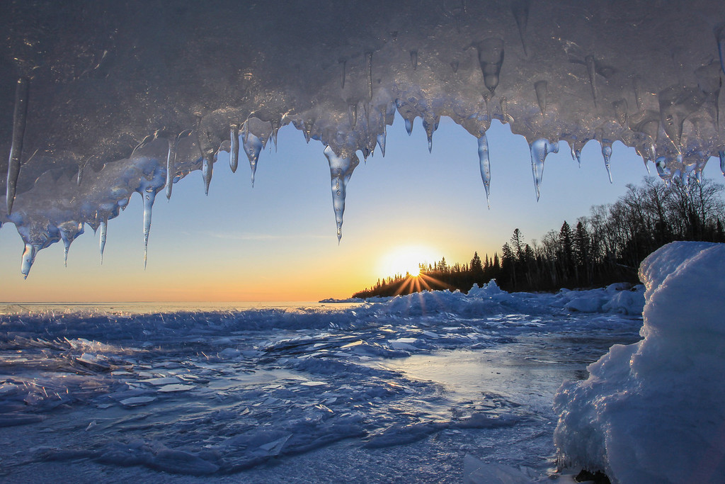 "FRIDAY, FEBRUARY 22, 2013<br /> <br /> SUPERIOR WINTER 0795<br /> <br /> ""Ice Cave Sunset""<br /> <br /> This view was the perfect end to a beautiful day.  I had spent a couple of hours photographing ice along the shoreline when I came across this small cave.  The cave had a rock in it that was just the right size and shape to make a comfortable seat.  When I sat down on the rock inside the cave, the view looking back out along the shoreline was magical.  The sun was just starting to dip below the trees and the hanging ice framed the scene beautifully.  Like I said earlier... the perfect end to a beautiful day! <br /> <br /> Camera: Canon EOS 5D Mark II<br /> Lens: Canon EF 17-40mm<br /> Focal length: 17mm<br /> Shutter speed: 1/125<br /> Aperture: f/22<br /> ISO: 400"