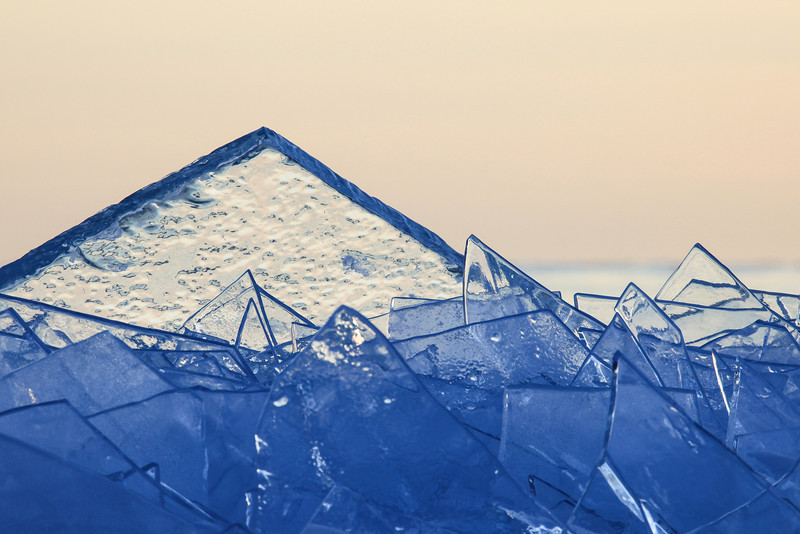 "WEDNESDAY, FEBRUARY 20, 2013<br /> <br /> ABSTRACT 0802<br /> <br /> ""Lake Superior Pyramid""<br /> <br /> Whoa, did I ever have fun photographing ice today!  I went back to the place where I photographed sunset last night, and it sure was a different experience.  Compared to last night's wild winds and awesome clouds, today there were no clouds and the air couldn't have been calmer.  There was a light swell rolling in off the lake, and the only sounds were coming from the water as it gurgled beneath the ice.  Occasionally one of the ice plates would shift and you would hear it fall, a sound I can only say is not unlike the sound of breaking glass.  I found many formations of ice sticking up into the air like the one you see here.  I had a lot of fun isolating different areas of the ice against the sky.  I hope this ice hangs on for a while, as I'd really like to spend more time photographing there. <br /> <br /> Camera: Canon EOS 5D Mark II<br /> Lens: Canon EF 100-400mm<br /> Focal length: 400mm<br /> Shutter speed: 1/125<br /> Aperture: f/16<br /> ISO: 400"