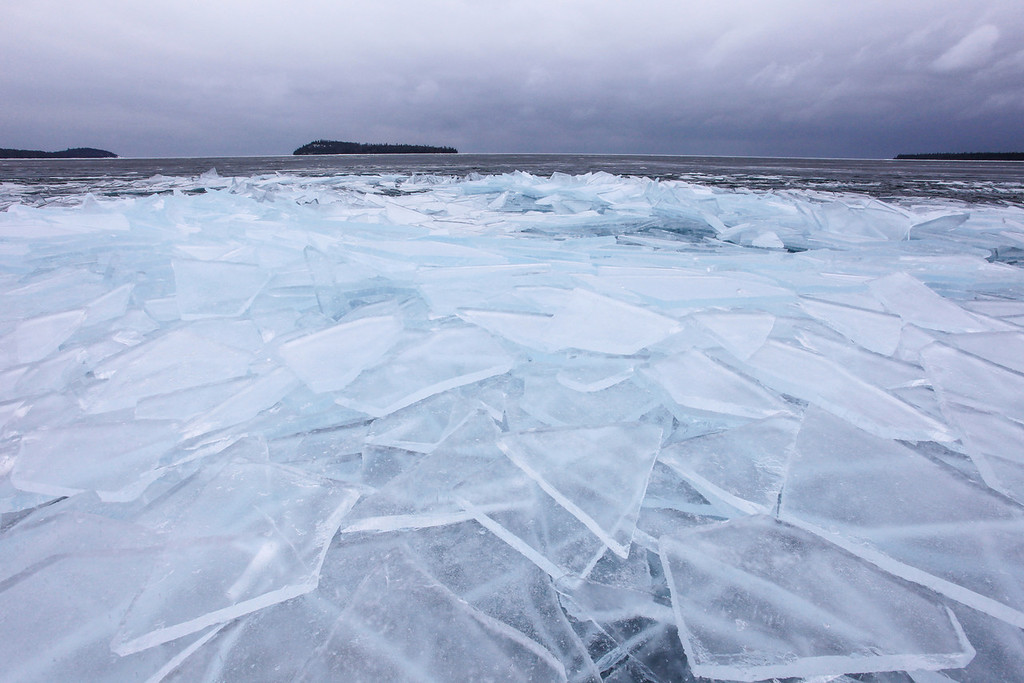 """TUESDAY, FEBRUARY 12, 2013<br /> <br /> SUPERIOR WINTER 0543<br /> <br /> """"Ice Paradise - Grand Portage Bay""""<br /> <br /> This past weekend we had a nice surprise on Grand Portage Bay.  Saturday morning we woke to all these amazing blue ice sheets that had been pushed up along the shoreline in the night.  Almost the entire bay was ringed with these sheets of ice.  Armed with my ice spikes on my boots I walked along the shore and took in the amazing sight of this icy paradise.  Unfortunately the view you see here was short-lived.  Sunday night we had a major blizzard combined with high winds.  The combination of wind and snow dramatically changed this view.  Some of the ice sheets are still there, but the waves broke them up quite a bit and they are now covered in snow.  Today there is a fresh layer of ice on the bay and I can hear it crunching as it gets pushed up on shore once again.  So, maybe we will have fresh views again similar to this one!  One never knows what Lake Superior will do to surprise you in the winter season :-) <br /> <br /> Camera: Canon EOS 5D Mark II<br /> Lens: Canon EF 17-40mm<br /> Focal length: 17mm<br /> Shutter speed: 1/200<br /> Aperture: f/16<br /> ISO: 400"""