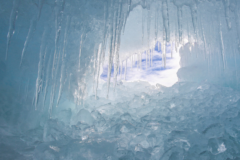 "THURSDAY, FEBRUARY 28, 2013<br /> <br /> SUPERIOR WINTER 0883-2<br /> <br /> ""Cave of Cubes""<br /> <br /> Check out this recent photo I made of a small ice cave on the shores of Lake Superior filled with ice cubes from the lake.  I think it's pretty ""cool"".  It was a fun find and very difficult to photograph because the cave was so small.  It was only about two feet from the cave bottom to the cave top, and I had to literally lay on the ground and sort of slide down into the cave head first.  I then had to hold my camera up and shoot blindly since I was physically unable to look through the viewfinder due to the way I was laying in the cave.  It was also kind of difficult to extract myself from the cave since I was, after all, surrounded by ice.  Every surface in sight was extremely slippery and it was a challenge to push myself backwards uphill to get out of the cave.  Luckily my friend Roger was shooting with me that day and if I had gotten stuck I'm sure he would have helped me out :-) <br /> <br /> Camera: Canon EOS 5D Mark II<br /> Lens: Canon EF 17-40mm<br /> Focal length: 17mm<br /> Shutter speed: 1/40<br /> Aperture: f/16<br /> ISO: 200"