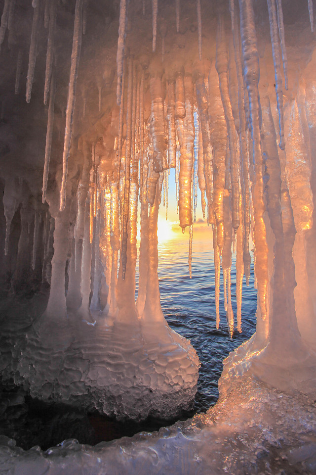 "SUNDAY, FEBRUARY 17, 2013<br /> <br /> SUPERIOR WINTER 0626<br /> <br /> ""Ice Cave Sunrise""<br /> <br /> There is so much good ice along the north shore of Lake Superior right now, I'm sort of wishing I didn't have a day job so I could spend all day every day exploring and photographing the ice!  This is another shot from yesterday morning's sunrise near Cascade River State Park.  This cave wasn't very big.  I basically crawled into it head first then turned on my side to make photographs of the sun rising behind the icicles.  I sure love the color of the ice as the sun illuminated it from behind.  What a beautiful sight! <br /> <br /> Camera: Canon EOS 5D Mark II<br /> Lens: Canon EF 17-40mm<br /> Focal length: 17mm<br /> Shutter speed: 1/40<br /> Aperture: f/16<br /> ISO: 200"