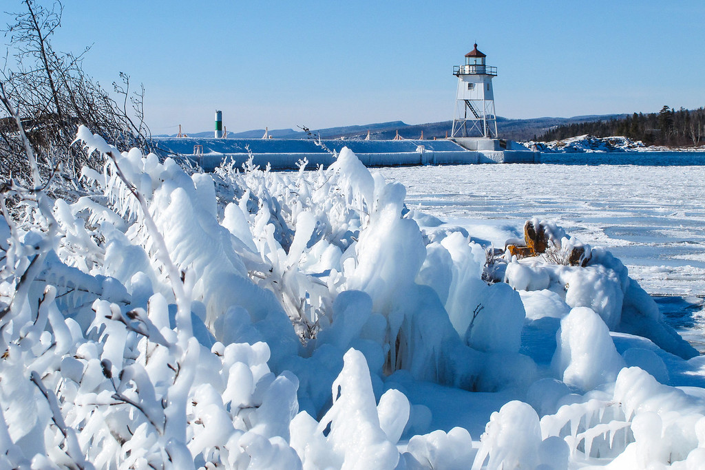 """MONDAY, FEBRUARY 4, 2013<br /> <br /> SUPERIOR WINTER 4740<br /> <br /> """"Icy Paradise - Grand Marais Lighthouse""""<br /> <br /> A favorite shot from this weekend's ice exploration adventure between Grand Marais and Grand Portage.  Artist's Point was a winter wonderland of ice!  We had great fun crawling around on our bellies taking macro shots of all the frozen pools of water on the lakeside of the point, then we discovered that the harbor side of the point was even more amazing, with every shrub in sight coated in a thick layer of ice!  We spent a good hour exploring all the different compositions we could find within this little frozen forest.  This shot, framed with the lighthouse in the background, was one of my favorites from this area.   <br /> <br /> Camera: Canon PowerShot G11<br /> Focal length: 15.673mm<br /> Shutter speed: 1/2000<br /> Aperture: f/5.6<br /> ISO: 200"""