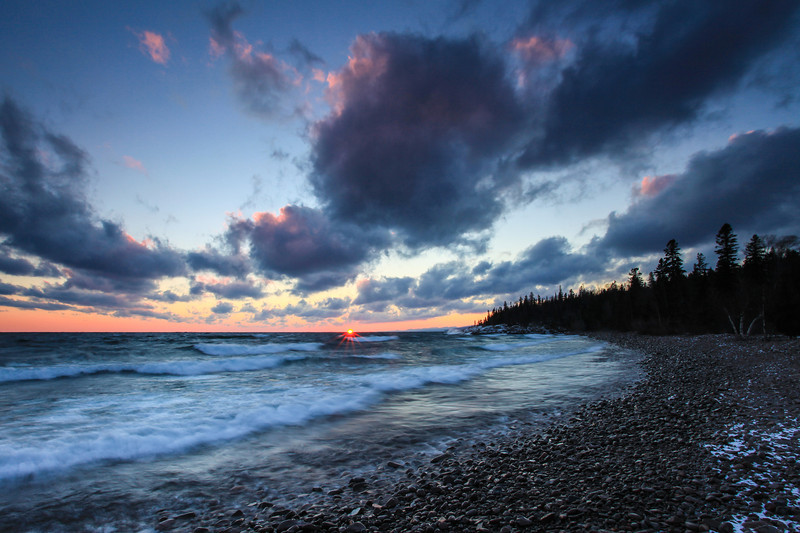 "WEDNESDAY, JANUARY 16, 2013<br /> <br /> SUPERIOR WINTER 9845<br /> <br /> ""Sundown - Grand Marais, Minnesota""<br /> <br /> Here is another shot from last night's EXTREMELY windy sunset in Grand Marais.  This was the very first shot that I made when arriving at this beach.  I got there just in time to see the sun for a few seconds as it was dropping out of sight below the horizon.  The waves were awesome and I don't think I've ever seen the clouds moving so quickly before.  I spent another 30 to 40 minutes taking pictures here after this initial shot.  My favorite of the evening was ""Superior Waterfall"" which I posted yesterday, but I also like this one and wanted to share it as well. <br /> <br /> Camera: Canon EOS 5D Mark II<br /> Lens: Canon EF 17-40mm<br /> Focal length: 17mm<br /> Shutter speed: 0.5 sec<br /> Aperture: f/22<br /> ISO: 200"