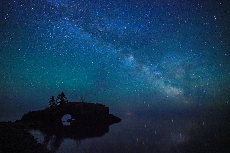 "SUNDAY, JUNE 9, 2013<br /> <br /> MILKY WAY 4249<br /> <br /> ""Superior Galaxy""<br /> <br /> Here is a shot I have been wanting to capture for some time, the Milky Way Galaxy over Hollow Rock on the shores of Lake Superior.  This was taken at 12:02 AM on June 9, 2013.  The stillness of the night was unbelievable.  Rarely have I seen Lake Superior so calm and never before have I seen the stars reflecting so nicely in the waters of the big lake.  The sight you see here is a vivid memory that will live forever in our minds.  I owe thanks to Jessica for this photo, for it was at her urging that we went out to photograph the Milky Way on this most exquisite of nights!<br /> <br /> Camera: Canon EOS 5D Mark II<br /> Lens: Canon EF 17-40mm<br /> Focal length: 17mm<br /> Shutter speed: 30 seconds<br /> Aperture: f/4<br /> ISO: 6400"