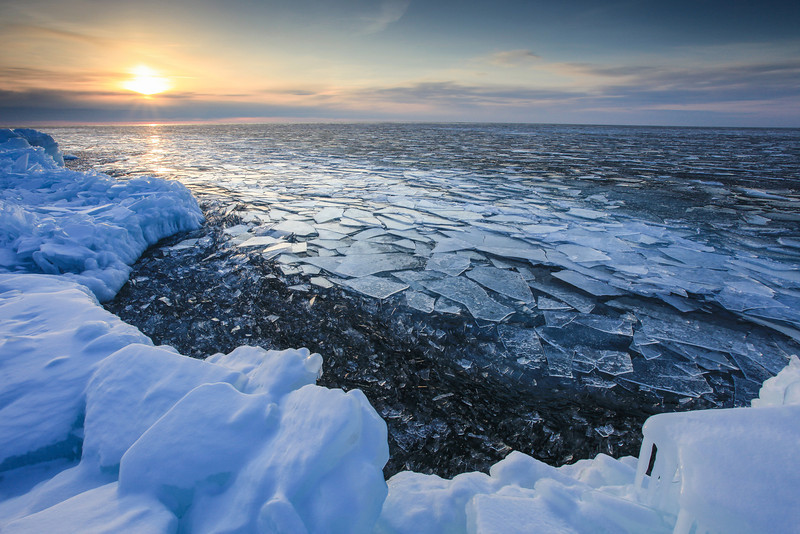 "FRIDAY, MARCH 8, 2012<br /> <br /> SUPERIOR WINTER 1220<br /> <br /> ""Plate Ice Sunrise, Whitecaps Point""<br /> <br /> As promised, here is another shot from this morning's sunrise over Lake Superior.  Whitecaps Point (not an official name, just a name I came up with to reference this area) was lined with beautiful plate ice this morning.  Soft swells were rolling in off the lake, and the plates of ice were rubbing against each other in the swells, making a magical ""shooshing"" sound.  It was a gentle sound, not loud and abrasive like the sound made when the plates are piling up against the shore.  I sure do love this time of year and wish it lasted longer.  Spring is on its way, though, and soon I will be heading to the canyonlands of the southwest for a 3-week camping/hiking/biking adventure honeymoon with the love of my life! <br /> <br /> Camera: Canon EOS 5D Mark II<br /> Lens: Canon EF 17-40mm<br /> Focal length: 17mm<br /> Shutter speed: 1/40 sec<br /> Aperture: f/16<br /> ISO: 200"