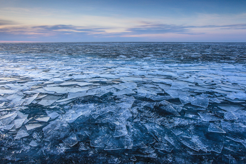 "MONDAY, MARCH 11, 2013<br /> <br /> SUPERIOR WINTER 1212<br /> <br /> ""Endless Ice""<br /> <br /> Here is a recent shot of plate ice on Lake Superior, extending out as far as the eye can see.  It sure was an interesting morning to be out exploring the shoreline.  There was a wind coming off the lake along with a gentle swell that made the ice fascinating to watch.  As each swell rolled in to shore you could see the plates of ice gently moving up and down with each passing wave.  It was a very gentle movement, and to me looked as though you could see the lake breathing.  With each wave the ice would rise, then fall.  It was as if each passing wave was the lake taking a breath, then exhaling.  This photo was made at sunrise.  I returned to this same location at sunset and all the plate ice was gone.  After a full day of being ground against each other by the waves the plates of ice had been ground down to small chunks of ice that ""tinkled"" against each other as they rolled in the waves that were still coming in throughout the evening. <br /> <br /> Camera: Canon EOS 5D Mark II<br /> Lens: Canon EF 17-40mm<br /> Focal length: 21mm<br /> Shutter speed: 1/13 sec<br /> Aperture: f/16<br /> ISO: 200"