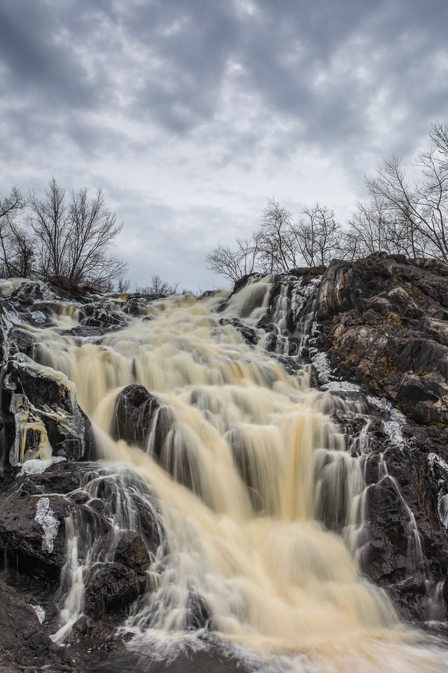 """FRIDAY, NOVEMBER 22, 2013<br /> <br /> RIVERS 4908<br /> <br /> """"Kawishiwi Falls""""<br /> <br /> Earlier this week Jessica and I were in Ely, MN """"playing tourist"""" for a day.  We had a great time walking the main street of Ely and checking out such places as the Brandenburg Gallery, the Piragis Northwoods Company store and the Steger Mukluks store.  We also enjoyed a delicious lunch at """"A Taste of Ely"""", a very nice local cafe that also features live music and a small art gallery.  The first item on our agenda for that day, however, was a hike to Kawishiwi Falls, a beautiful waterfall located just a few miles outside of town.  The hike to the waterfall was easy, winding through a very nice forested area.  Even though it was a very overcast day we were lucky enough to have some nice definition in the cloud cover, making for a nice shot from near the base of the falls.  I would highly recommend the easy hike to this waterfall if you are ever in the Ely area!<br /> <br /> Camera: Canon EOS 5D Mark II<br /> Lens: Canon EF 17-40mm<br /> Focal length: 35mm<br /> Shutter speed: 0.4 sec<br /> Aperture: f/22<br /> ISO: 50"""
