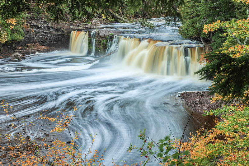 "TUESDAY, OCTOBER 15, 2013<br /> <br /> MICHIGAN 2542<br /> <br /> ""Foam Trails, Manabezho Falls""<br /> <br /> Another beautiful waterfall on the Presque Isle River!  This one is named ""Manabezho Falls"" and, according to signage along the trail, is the largest waterfall on the river.  It was getting very late in the evening when I photographed this waterfall.  As such, it was easy to take long exposures of the falls.  This one ended up being 6 seconds and gave me some very nice ""foam trails"".  I love taking long exposures of rivers and showing the movement of the water.  It's one of the funnest things you can do with a camera!<br /> <br /> Camera: Canon EOS 5D Mark II<br /> Lens: Canon EF 24-105mm<br /> Focal length: 65mm<br /> Shutter speed: 6 seconds<br /> Aperture: f/22<br /> ISO: 50"