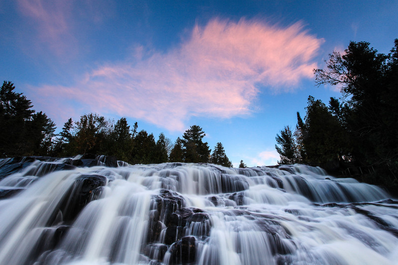 "SUNDAY, OCTOBER 13, 2013<br /> <br /> MICHIGAN 2104<br /> <br /> ""Autumn Sunset over Bond Falls""<br /> <br /> Here is another shot from Bond Falls, this time at sunset.  This was the second round of color that occurred in the clouds.  Everyone knows that as the sun sets, the clouds often light up in spectacular fashion with amazing colors.  Fewer people know that there is sometimes a second round of color that happens anywhere from 10 to 30 minutes after that initial round of color fades away.  That is what happened on this night.  I thought ""the show"" was over after the initial sunset was over, but then another round of clouds moved in.  <br /> <br /> All too often I've been photographing in a location and seen other photographers pack up and leave as soon as the first round of color is over.  I like to stick around and see what happens.  Often times my favorite images are made AFTER sunset, when the light and color is more subtle.  As this cloud drifted over the top of the falls, it started to glow with a pinkish hue.  This glow only lasted 2 or 3 minutes, then it was gone.  From scouting out the falls earlier in the evening I knew that in order to get the sunset shot I wanted I would have to be standing in the water.  So, I had changed back at the car before sunset and was wearing my shorts and sandals so I could walk out into the water and get close to the base of the falls. I was standing in about 6 inches of water just 10 feet away from the base of the falls to make this photograph.  Sometimes you've got to get your feet wet to get the best shot :-)<br /> <br /> Camera: Canon EOS 5D Mark II<br /> Lens: Canon EF 17-40mm<br /> Focal length: 17mm<br /> Shutter speed: 0.8 seconds<br /> Aperture: f/16<br /> ISO: 400"
