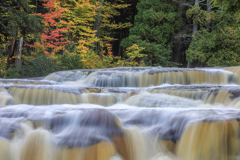 """SATURDAY, OCTOBER 12, 2013<br /> <br /> MICHIGAN 2659<br /> <br /> """"A touch of color at Manido Falls""""<br /> <br /> Okay, here is the first image that I am sharing from the Upper Peninsula of Michigan.  This is a close-up shot of one small section of Manido Falls on the Presque Isle River in Porcupine Mountains Wilderness State Park.  I was enthralled by this waterfall!  I spent a total of about 3 hours photographing this waterfall, 1 hour at dusk and 2 hours at dawn.  There is just so much variety to it.  It is a long waterfall with several steps and cascades.  I spent a lot of time with my 100-400mm telephoto lens isolating different areas of the falls.  I can't wait to go back and camp at this park and explore more of the wonderful beauty that it has to offer!<br /> <br /> Camera: Canon EOS 5D Mark II<br /> Lens: Canon EF 100-400mm<br /> Focal length: 130mm<br /> Shutter speed: 0.5 seconds<br /> Aperture: f/22<br /> ISO: 50"""