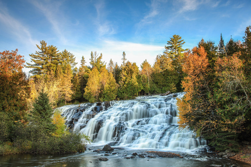 "SUNDAY, OCTOBER 13, 2013<br /> <br /> MICHIGAN 2039<br /> <br /> ""October Morning at Bond Falls""<br /> <br /> Boy, the U.P. sure has some awesome waterfalls!  Like Manido Falls on the Presque Isle River, Bond Falls is a place where I easily spent several hours photographing the many cascading sections of the falls.  There is about a 1/4 mile long section of river that has lots of little waterfalls culminating in the larger drop that you see in this photo.  The Michigan DNR has constructed a very nice accessible boardwalk area that forms a huge arc along the bottom of the falls so people of all abilities can enjoy the falls from almost any angle.  This photo was taken from that boardwalk.  I was very fortunate to have an interesting sky with some nice clouds on the one morning that I was able to spend at the falls!<br /> <br /> Camera: Canon EOS 5D Mark II<br /> Lens: Canon EF 24-105mm<br /> Focal length: 32mm<br /> Shutter speed: 1.3 seconds<br /> Aperture: f/16<br /> ISO: 50"