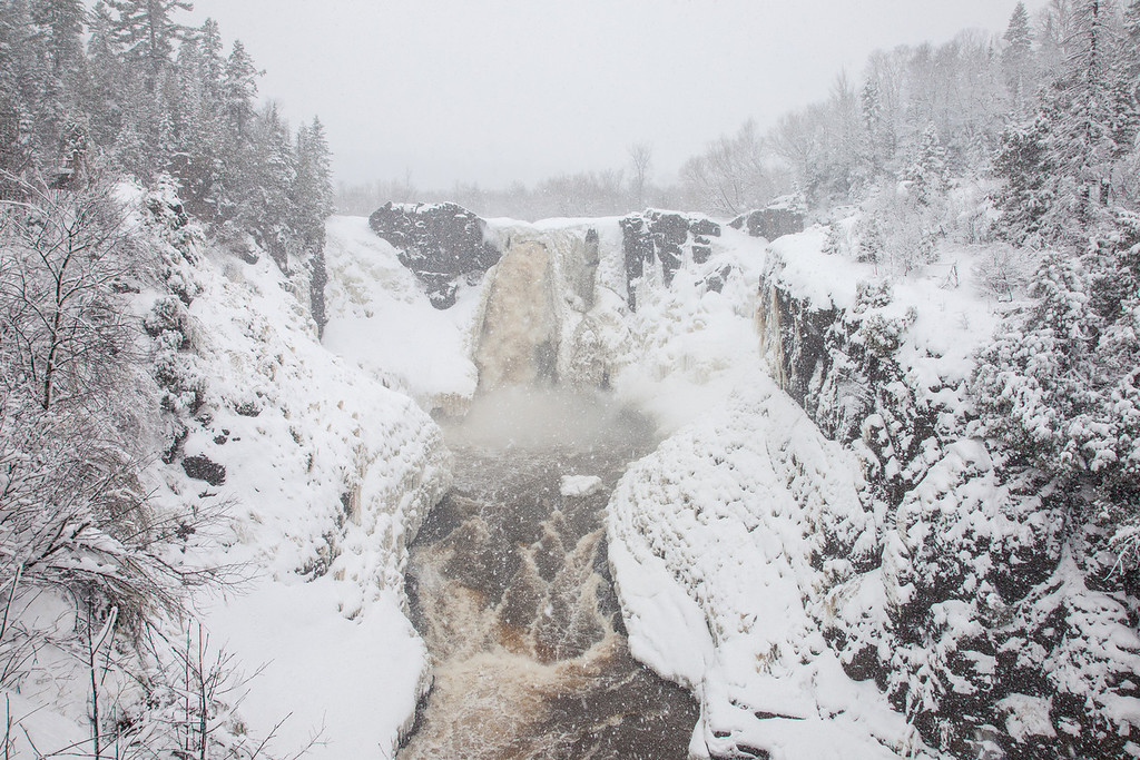 "FRIDAY, APRIL 18, 2014<br /> <br /> PIGEON RIVER 3441<br /> <br /> ""Spring Blizzard at High Falls""<br /> <br /> Over the past couple of weeks I've been trying to visit High Falls every day to document the changes as the river opens up from its deep freeze.  Each day presents a very different view at the falls.  This is yesterday's view.  We had a proper spring blizzard yesterday that dumped about a foot of new snow on us.  Originally our forecast called for about an inch of new snow but the storm track changed and all of a sudden they were saying we might get a foot!  Well, they were right.  It was a heavy, wet snow but it sure was beautiful in the woods while it was snowing.  I got absolutely soaked trudging through the deep snow while getting bombarded from above by the continuing heavy rate of wet snowfall.  This shot was worth it, though!  I'm anxious to get up there again today and see what the view looks like in today's sunshine!  <br /> <br /> Camera: Canon EOS 5D Mark II<br /> Lens: Canon EF 24-105mm<br /> Focal length: 24mm<br /> Shutter speed: 1/200<br /> Aperture: f/16<br /> ISO: 800"