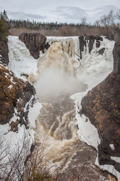 """SUNDAY, APRIL 13, 2014<br /> <br /> PIGEON RIVER 3091<br /> <br /> """"Opening Up!""""<br /> <br /> High Falls of the Pigeon River is running!  It opened up several days ago and with each day more ice fades away and the water flow increases.  The """"big break up"""" of ice has yet to occur, but that should be happening any day now!  It's an exciting time of year for waterfall watching!<br /> <br /> Camera: Canon EOS 5D Mark II<br /> Lens: Canon EF 24-105mm<br /> Focal length: 35mm<br /> Shutter speed: 1/15<br /> Aperture: f/22<br /> ISO: 50"""