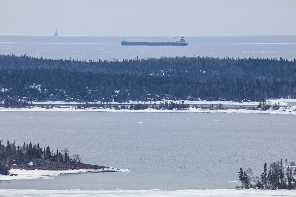 "WEDNESDAY, APRIL 16, 2014<br /> <br /> SUPERIOR BOATS 3291<br /> <br /> ""Freighter passing the Susie Islands and Rock of Ages Lighthouse""<br /> <br /> I got a new lens yesterday and today I went out and about to try it out.  So far, I love it!  It's the new Tamron 150-600, and boy is it a nice lens!  It's a little bigger and just slightly heavier than my Canon 100-400 (which is to be expected) but it still fits in my camera backpack.  I love the extra reach that the Tamron provides.  So far I'm finding the images to be just as sharp as anything shot with my 100-400.  The photo shown here is one of the first images I made today with the Tamron.  It was taken from the Susie Islands overlook along Highway 61 in Grand Portage.  There were actually 3 freighters passing by at the time.  Each boat had a different design and I think this one had the most pleasing profile of the 3.  So, I waited for it to get between the Susie Islands and Rock of Ages Lighthouse then made this picture.  I don't know which freighter it was, but I'm pretty sure it's a Canadian ship from the Algoma Central Corporation, as it looks like their symbol on the stack at the rear of the ship.  <br /> <br /> Camera: Canon EOS 5D Mark II<br /> Lens: Tamron SP 150-600mm<br /> Focal length: 600mm<br /> Shutter speed: 1/320<br /> Aperture: f/16<br /> ISO: 400"