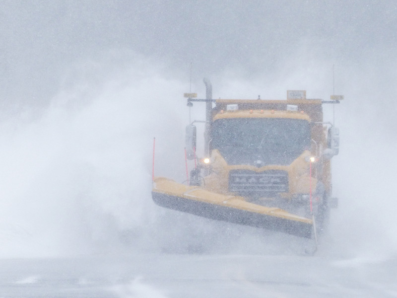 """TUESDAY, APRIL 1, 2014<br /> <br /> GRAND PORTAGE 1030799<br /> <br /> """"Cook County Blizzard Buster""""<br /> <br /> I know, I know… everyone is sick of winter.  Well, my patience is running a little thin for the season as well but as long as it continues to provide for some good photo opportunities, I'm not going to pass them up!  Just a little while ago it was snowing pretty hard here in Grand Portage.  It is also very windy.  I was outside shoveling when I heard the county plow truck pass by on the road behind our house.  I knew this meant in another minute or so it would be coming by the front of our house.  With the snow blowing across the roadway I knew it would make for an interesting shot of the plow truck.  So, I went in the house to get the camera then went back outside and positioned myself near the end of the driveway.  Sure enough, about 20 seconds later, the truck came around the corner and it was just annihilating the drifts that were on the roadway.  When the blade hit a drift, the snow would fly up and the wind would catch it and whip it everywhere.  I made this photo just as the plow was hitting a drift and the wind was doing its thing.  It sure made for a pretty impressive picture!<br /> <br /> Camera: Panasonic DMC-FZ200<br /> Focal length: 600mm<br /> Shutter speed: 1/1250<br /> Aperture: f/6.3<br /> ISO: 200"""