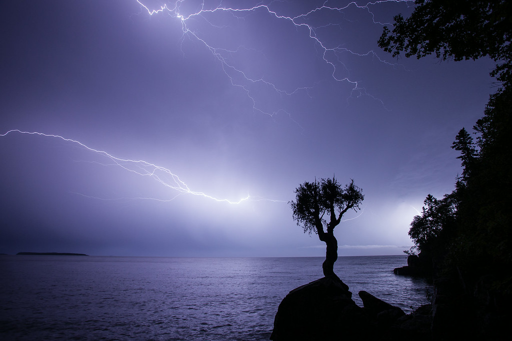 "MONDAY, AUGUST 25, 2014<br /> <br /> LIGHTNING 9263<br /> <br /> ""Late Summer Storm over Wauswaugoning Bay""<br /> <br /> Here is another image from last night's incredible lightning storm.  After shooting the storm from our yard for a while the lightning was still going off frequently but had moved further out over the lake beyond Hat Point.  The rain had let up and was really not much more than a sprinkle.  So, I decided to head down to the spirit tree and try photographing the storm from there.  I got there just in time to capture this image, making just 4 or 5 exposures before capturing this one.  It was the only good shot I came away with.  The best of the lighting was done.  Flashes of light still illuminated the clouds every few seconds or so but the bolts were not coming anymore.  Thankfully I headed down there when I did otherwise I wouldn't have this image!  This was shot with the camera in Bulb mode. Exposure length was 21 seconds at f/8 and ISO 400.<br /> <br /> Camera: Canon EOS 5D Mark II<br /> Lens: Canon EF 17-40mm<br /> Focal length: 17mm<br /> Shutter speed: 21 seconds<br /> Aperture: f/8<br /> ISO: 400"