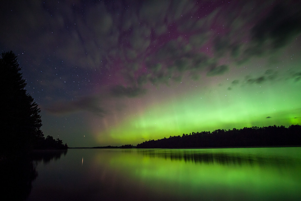 "FRIDAY, AUGUST 29, 2014<br /> <br /> AURORA 9325<br /> <br /> ""Vermilion Aurora""<br /> <br /> I just returned from two nights spent in Ely, MN and was lucky enough to have a nice aurora display while I was there!  Jessica was working there for the week and had a day off so I went up to spend the day with her.  We played tourist for the day, spending the morning at the International Wolf Center and the afternoon driving around exploring the area.  I knew that there was a good chance of aurora activity for Wednesday night so in the afternoon we drove around checking out various water accesses to find a good spot for photographing the aurora.  The location I liked most was within the newly established Lake Vermilion State Park.  This is Minnesota's newest state park and isn't even ""officially"" open yet, with no signs at all advertising the park or its location.  They are working on a new entrance road, however, so there is some access available.  We drove to the end of the new road and found a nice picnic area with some trails that are being developed along the lake.  There is a nice new fishing pier that faces to the north which we knew would make a great spot for aurora watching.  So, I decided that this was going to be the place where I would return that night to watch for the lights.  <br /> <br /> I returned to the site at about 11 PM and when I arrived the lights were already in full swing, dancing throughout the sky.  Some light cloud cover did obstruct the view of the lights somewhat but after only a few minutes the clouds started to dissipate and made a nice complement to the view of the lights.  Before long the sky was completely clear but the lights had faded to a dull glow.  I decided to wait it out for at least a few hours and see if they would pick back up.  As I waited I was treated to the always glorious sounds of several pairs of loons calling from various areas around the lake.  I know there were at least two pairs, possibly 3 that I was hearing.  The air was unbelievably calm so the calls from the loons echoed for miles around.  Around 1:45 AM it seemed the lights were starting to get brighter so I started making exposures again.  Before long the sky was bright with the slow moving glow that is characteristic of a mild geomagnetic storm.  I watched as a small arc grew in size over the opposite shore of the lake.  The arc got bigger and bigger until it eventually no longer fit within the field of view of my 17mm lens.  Every now and then vertical pillars of light appeared within the arc and shot upwards into the sky, carrying amazing hues of red and purple light. Somewhere between 2:30 and 3:00 AM the lights faded back to a dull glow and I was starting to get pretty tired so I called it a night and headed back to the hotel in Ely.  This new state park sure makes a great location for watching the night sky.  There is hardly any light pollution at all and with the park being on the south shore of the lake, it's a prime location for watching the Aurora Borealis!  <br /> <br /> Camera: Canon EOS 5D Mark II<br /> Lens: Canon EF 17-40mm<br /> Focal length: 17mm<br /> Shutter speed: 30 seconds<br /> Aperture: f/4<br /> ISO: 1600"