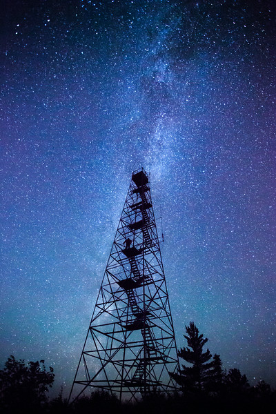 "FRIDAY, AUGUST 1, 2014<br /> <br /> MILKY WAY 8793<br /> <br /> ""Within the Milky Way""<br /> <br /> The other night after shooting the Milky Way from the pines I headed to another favorite night sky location of mine where there is an old fire tower.  It's fun photographing the fire tower with the Milky Way rising alongside it.  This time, though, I wanted to see what it would look like with the Milky Way behind the tower.  Once I did a test shot and saw what it was like, I decided to lock the shutter button down on the camera so it would take one exposure after another. Then, I climbed the tower and stood at various levels to get myself in the shot as well.  This is the image that I thought was the best. I am standing on a platform a little over halfway up the height of the tower.  This is where my silhouette seemed to show up the best.  I really like the way this shot turned out.  Viewing the Milky Way from the tower was incredible.  It felt like I could reach out and pluck the stars right out of the sky, almost like I was within the Milky Way itself (which we are, actually).  Thus, my title for this image ""Within the Milky Way"" was born :-)<br /> <br /> Camera: Canon EOS 5D Mark II<br /> Lens: Canon EF 17-40mm<br /> Focal length: 17mm<br /> Shutter speed: 30 seconds<br /> Aperture: f/4<br /> ISO: 6400"