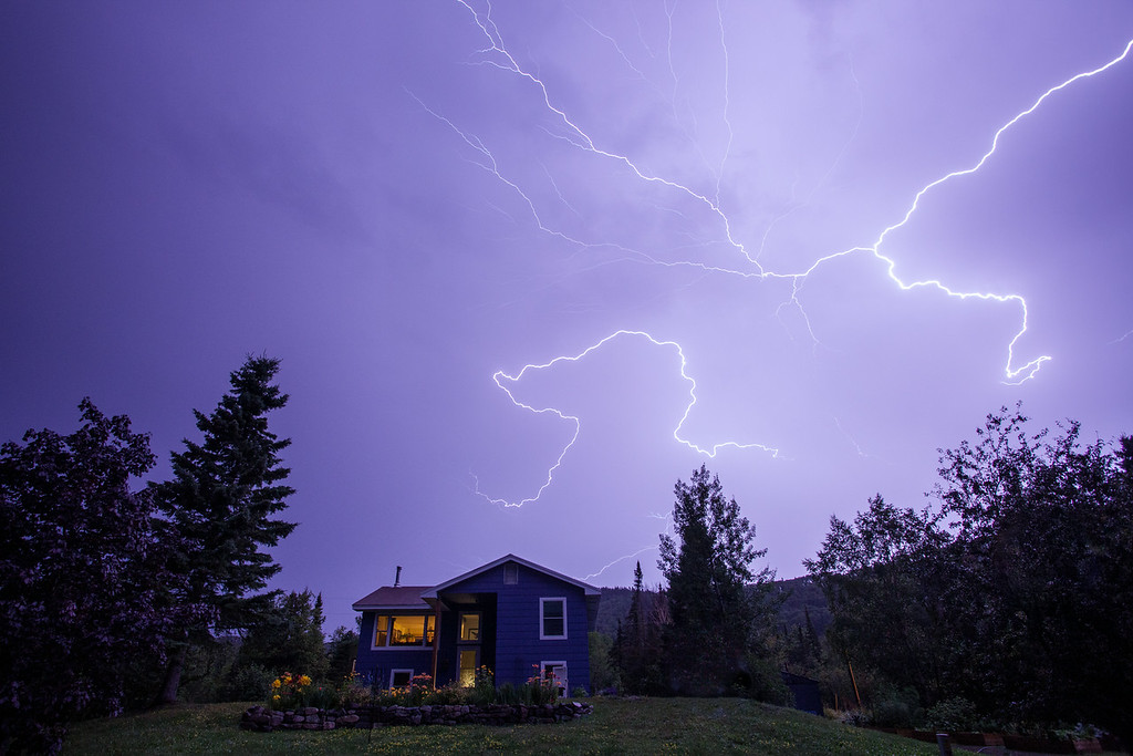 "MONDAY, AUGUST 25, 2014<br /> <br /> LIGHTNING 9255<br /> <br /> ""Late Summer Storm""<br /> <br /> Last night we had one heck of a line of thunderstorms come through Grand Portage.  I was watching the radar as the storms approached and it sure looked like we were in for something special.  The weather hit Grand Portage Bay about 12:30 AM.  It started with a soft breeze and light rain which quickly turned to gusty winds and a downpour.  At first I tried photographing the lightning over the lake from underneath the overhang in front of our house.  That didn't work as the rain was coming sideways and I got pretty wet after just a minute or two.  So, I went back in the house and watched the light show from the living room window.  <br /> <br /> After about 10 minutes the rain had pretty much stopped but the lightning was still going off like crazy.  So, I went back outside and quickly noticed that the lightning was actually better behind the house.  I walked down to the road and photographed the flashes of light over the house.  Every now and then an extra bright flash accompanied by a strong bolt would light up the sky.  The photo you see here was the best out of the series of roughly 30 images that I shot.  I was shooting in Bulb mode and this ended up being a 6 second exposure at f/8 and ISO 800.  After a few minutes of shooting from the road, the rain started up again and continued for about the next hour.  When it let up again I checked our rain gauge and it showed almost an inch of new rainfall!<br /> <br /> Camera: Canon EOS 5D Mark II<br /> Lens: Canon EF 17-40mm<br /> Focal length: 17mm<br /> Shutter speed: 6 seconds<br /> Aperture: f/8<br /> ISO: 800"