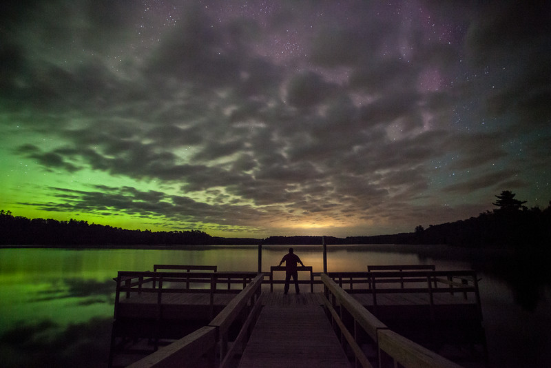 "SATURDAY, AUGUST 30, 2014<br /> <br /> AURORA 9346<br /> <br /> ""Front row seat for the aurora show""<br /> <br /> Here is another image from the northern lights display that I saw over Lake Vermilion in the early morning hours of August 27th.  This was before the clouds had moved out and before the lights were really good.  The aurora color here was actually incredibly faint but shooting a 30 second exposure at ISO 6400 really brought the colors out.  This is a self-portrait of me standing on the fishing pier at Lake Vermilion State Park looking in the direction of the town of Ely.  The orange-colored light is actually the city glow from Ely reflecting off the bottom of the clouds.<br /> <br /> Camera: Canon EOS 5D Mark II<br /> Lens: Canon EF 17-40mm<br /> Focal length: 17mm<br /> Shutter speed: 30 seconds<br /> Aperture: f/4<br /> ISO: 6400"