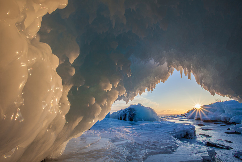 "MONDAY, FEBRUARY 10, 2014<br /> <br /> SUPERIOR WINTER 0664<br /> <br /> ""Whitecaps Point Ice Cave""<br /> <br /> We found a couple of cool north shore ice caves over the weekend.  The one shown here is the largest.  This one was about 15 feet deep and was tall enough that you could actually sit up inside it.  The other two that we found were pretty small and while you could crawl inside them it was difficult to take any decent picture from inside.  With my knowledge of the shoreline in Grand Portage, MN and how the sun lines up this time of year I figured this particular cave would make for a cool sunset shot.  I was right! <br /> <br /> Camera: Canon EOS 5D Mark II<br /> Lens: Canon EF 17-40mm<br /> Focal length: 17mm<br /> Shutter speed: 1/25<br /> Aperture: f/22<br /> ISO: 200"