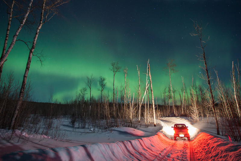 """SATURDAY, FEBRUARY 22, 2014<br /> <br /> AURORA 0840<br /> <br /> """"Aurora Drive""""<br /> <br /> Seeing the northern lights is always a special treat and the anticipation of seeing them is a feeling I never tire of.  On the evening of Tuesday, February 18th I was looking at my Facebook news feed before going to bed and noticed that a few people were saying they could see the northern lights.  So, I checked the forecast websites and sure enough, they indicated that it might be a good night to see some aurora activity.  This always leads me to walking out on our back deck and checking the north sky.  As soon as I got out on the deck and looked up, I could see the lights.  They were pretty faint, however, and I was pretty tired from an early morning photography outing followed by an afternoon of skiing.  Jessica, my lovely and ever-supportive wife, suggested I go to bed for a little while and set my alarm to wake me just after midnight to check the sky again.  So, that's what I did.  My alarm woke me at midnight, I checked the sky and the lights were really starting to flare up!  Next thing you know, I'm packing my gear and dressing for a night out in the winter woods.  I really need to thank my wife Jessica.  She not only tolerates my penchant for late-night aurora hunting but is also a strong supporter of it and always encourages me to go out and get some good photos.  <br /> <br /> So, just after midnight, I found myself driving down Highway 61 trying to figure out where to go to photograph the lights when I realized """"Oh yeah… I need to go back to that logging road where I went last time when the lights were faint.""""  The last time I went out looking for the lights I drove down a road that is normally NOT plowed in the winter, but it is this year because there is a logging operation down this road.  Along the road to the logging area, there are lots of really nice trees for photographing against the night sky.  Even the logging cut is a nice place to shoot from, as it p"""