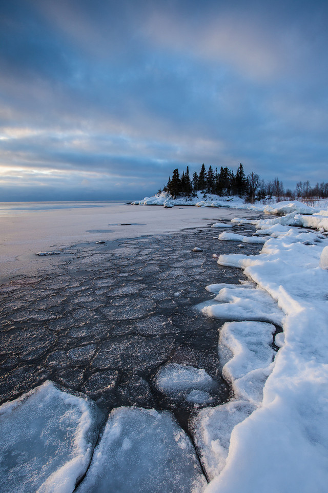 "SUNDAY, JANUARY 19, 2014<br /> <br /> SUPERIOR WINTER 0197<br /> <br /> ""January Ice at Coyote Point""<br /> <br /> Here is one from yesterday's morning on the Lake Superior shoreline in Grand Portage, MN.  I had a hard time deciding where I wanted to go to photograph the sunrise and as a result I almost missed it.  ALMOST, that is!  So, I quickly scouted the shoreline for a pleasing composition and found this curving section of ice that I knew would make a nice anchor for a vertical shot.   <br /> <br /> Camera: Canon EOS 5D Mark II<br /> Lens: Canon EF 17-40mm<br /> Focal length: 17mm<br /> Shutter speed: 1/13<br /> Aperture: f/16<br /> ISO: 200"