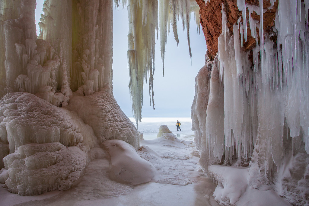 "THURSDAY, JANUARY 30, 2014<br /> <br /> APOSTLE ISLANDS 0362<br /> <br /> ""Sea Cave Ice - Apostle Islands National Lakeshore""<br /> <br /> Yesterday Jessica and I hiked the Lake Superior shoreline ice to visit the mainland sea caves at Apostle Islands National Lakeshore.  What an experience it was!  This was the first time visiting the caves for both of us.  It's not something you can do every year.  In fact it's been about 5 years since the last time the caves were safely accessible via the lake ice.  Some years the ice doesn't get thick enough or stable enough to make the trek to the caves.  You get there by taking an easy 1 mile hike east along the shoreline from the Meyers Beach access within the park.  Well, it was easy for us since it hasn't snowed in a while and thousands of people have visited the caves over the previous week or two, so the the snow was pretty hard-packed from all the foot traffic.  If you go right after a snow storm the hike would be more difficult.  <br /> <br /> After hiking about 1 mile along the shoreline you reach the cliffs and not long after that you start to see the caves.  Both the cliffs and the caves are fascinating.  Water seeps out of the rock face everywhere and creates beautiful hanging icicles.  It was a mind-blowing experience to see all these ice formations.  Very different from the north shore and the types of ice that I am used to seeing.  My favorite thing to do was to go inside the caves and photograph them from inside, looking out towards the lake.  Often I would wait for a person to walk by to add some depth and scale to the scene.  The sea caves and the ice were an incredible experience, you should go and check them out while you can.  Who knows, it might be another 5 years before they are accessible again!<br /> <br /> Camera: Canon EOS 5D Mark II<br /> Lens: Canon EF 17-40mm<br /> Focal length: 17mm<br /> Shutter speed: 1/200<br /> Aperture: f/16<br /> ISO: 400"