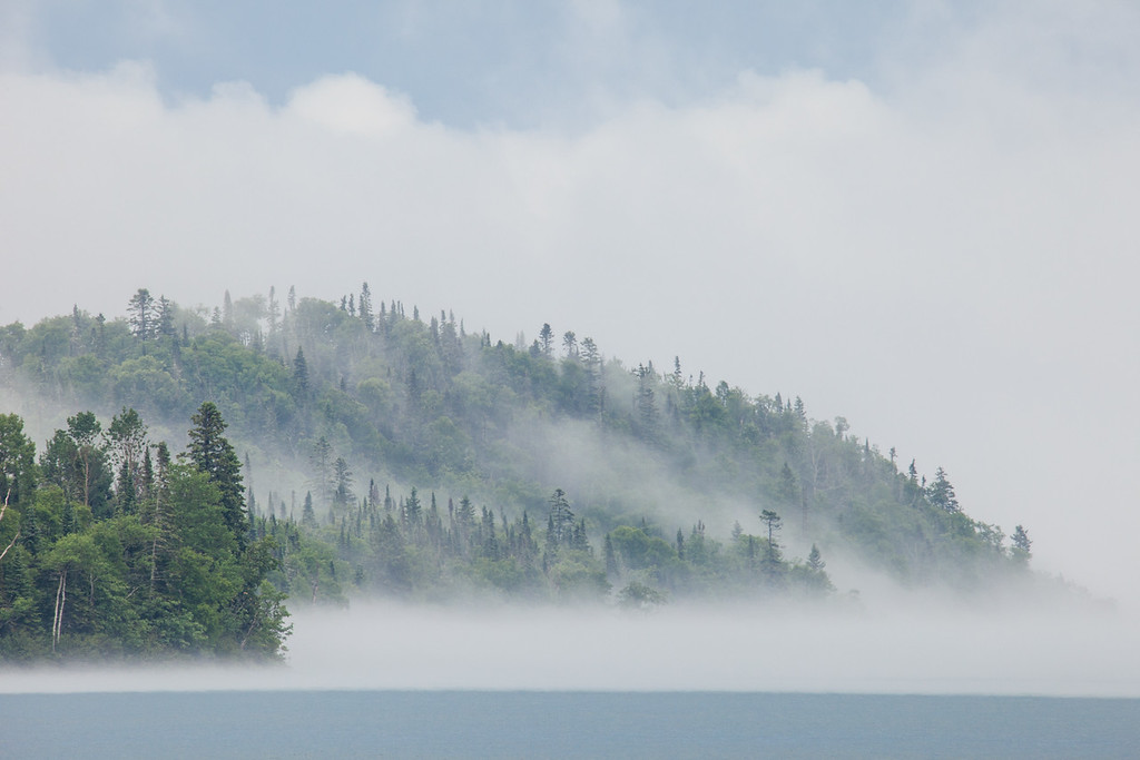 "SUNDAY, JULY 6, 2014<br /> <br /> SUPERIOR SUMMER 8185<br /> <br /> ""Fog over Hat Point""<br /> <br /> Yesterday we had a very stormy afternoon with lots of rain.  When it was all said and done we had accumulated about 2 inches of rainfall.  As I was driving home from work the fog was lifting off the bay and making for a really interesting scene over the tip of Hat Point.  I pulled over about a half mile from the house and made this image with my telephoto lens.  I love fog.  It is one of the most interesting things to photograph for sure!  It really adds a lot of depth to a scene.  This morning we are completely inundated with fog and I can barely see the lake in front of the house, let alone Hat Point about a mile away!<br /> <br /> Camera: Canon EOS 5D Mark II<br /> Lens: Tamron SP 150-600mm<br /> Focal length: 600mm<br /> Shutter speed: 1/30<br /> Aperture: f/16<br /> ISO: 400"