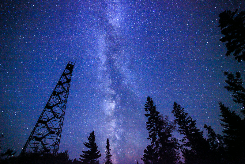 "MONDAY, JULY 21, 2014<br /> <br /> MILKY WAY 9275<br /> <br /> ""Fire Tower and the Milky Way Galaxy""<br /> <br /> I'm going through and reworking some of my Milky Way images.  When I first shot some of these I was still using Paint Shop Pro photo software which was limiting in how you could process the images.  Now that I'm using Lightroom I'm finding I can really get a lot more out of these images as my editing skills evolve.  When I compare this reworked image to the original way I had worked it up, I cannot believe that I ever let the original edit be seen.  This one is just so much better!  You could barely see the Milky Way in the first version.  In this one it really jumps out more.  This image will make a killer print!  This was taken on August 12, 2012 as some friends and I were sitting out watching the Perseid meteor shower.  I'm hoping for some nice clear skies again this year for watching the meteor shower, although the moon will be full so we may not see very many meteors anyway.  Either way, if it's a clear sky it will be a beautiful night!<br /> <br /> Camera: Canon EOS 5D Mark II<br /> Lens: Canon EF 17-40mm<br /> Focal length: 17mm<br /> Shutter speed: 30 seconds<br /> Aperture: f/4<br /> ISO: 6400"