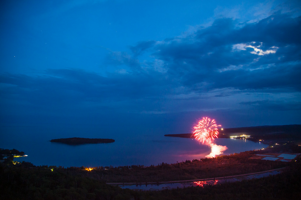 "SATURDAY, JULY 5, 2014<br /> <br /> FIREWORKS 8103<br /> <br /> ""4th of July 2014 over Grand Portage Bay""<br /> <br /> Last night Jessica and I chose to go away from the crowds and hiked up to the summit of Mt. Josephine to watch the fireworks.  We live about a mile or so from the trail so we took our mountain bikes and rode to the start of the trail then hiked up. We were a little concerned about the bugs, since the mosquitoes have been pretty bad this year.  Indeed, the bugs were pretty bad on the hike up and the hike down, but while we were at the summit there was a nice breeze from the west so they weren't too bad while watching the fireworks.  I just love the vantage point from the summit no matter what time of year, but it is extra cool to watch the fireworks from such a high viewpoint!  It's interesting to be looking down at them instead of up.  We had some nice moonlight to accompany the show and the moon illuminated the bay beautifully.  I hope everyone had a fun and safe 4th of July!<br /> <br /> Camera: Canon EOS 5D Mark II<br /> Lens: Canon EF 24-105mm<br /> Focal length: 24mm<br /> Shutter speed: 2.5 seconds<br /> Aperture: f/4<br /> ISO: 1600"