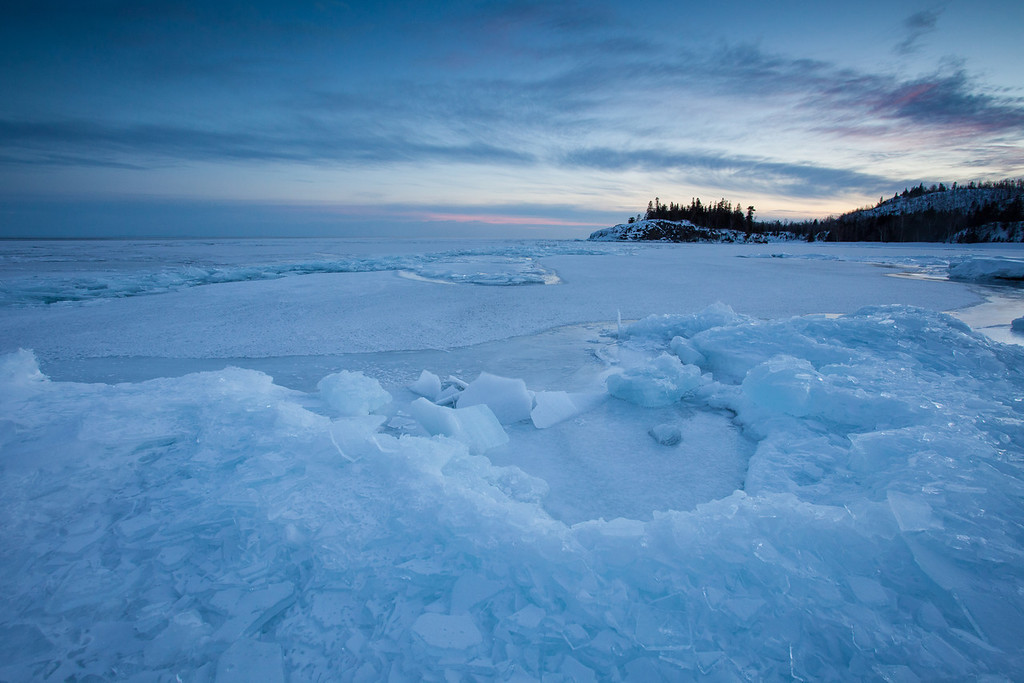 "MARCH 3, 2014<br /> <br /> SUPERIOR WINTER 1634<br /> <br /> ""March 1st ice on the Split Rock Lighthouse shoreline""<br /> <br /> This past weekend I was honored to be a presenter at a Lake Superior Photography Symposium put on by John Gregor of Coldsnap Photography and Split Rock Lighthouse.  Throughout the afternoon 3 other photographers in addition to myself presented their work to a group gathered in the auditorium at Split Rock Lighthouse.  It was a wonderful afternoon of sharing images, stories and techniques.  After the presentations we all went down to the shoreline just west of the lighthouse to photograph sunset.  Because of the clear and very cold conditions, sunset was rather bland.  But, it was still pretty out there.  Those extremely cold, crisp days have a stark beauty of their own.  The shoreline was packed in with ice so I looked for an interesting shape in the ice to put in the foreground of my photograph.  Not long after the sun went down we all made a quick escape to our vehicles due to the cold.  I'm not sure what the temp actually got down to for a low that night, but I know it was forecast to reach almost thirty below zero.  On the drive home I saw minus 15 on my truck's thermometer, and that was before 10 PM!  I can easily believe that it reached minus 30 later that night :-)<br /> <br /> Camera: Canon EOS 5D Mark II<br /> Lens: Canon EF 17-40mm<br /> Focal length: 17mm<br /> Shutter speed: 1/5<br /> Aperture: f/16<br /> ISO: 400"