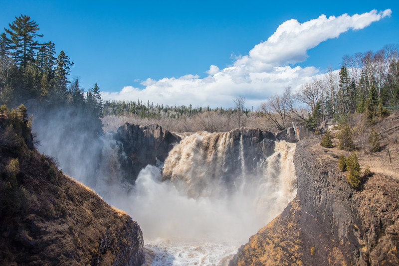 "MONDAY, APRIL 13, 2015<br /> <br /> PIGEON RIVER 3678<br /> <br /> ""What a difference a day makes!""<br /> <br /> Wow, some warm temperatures and some rain and 24 hours later High Falls in Grand Portage State Park is gushing!  It was starting to run pretty well yesterday, but after last night's rain and the temp pushing 60 today the waterfall is raging!  I visited the falls in the afternoon and was treated to an awesome end-to-end rainbow over the gorge from the west viewing deck.  It was quite a challenge keeping my lens dry to make these photos, as spray from the waterfall was constantly falling on the viewing decks.  I would say that waterfall season has officially begun :-)<br /> <br /> Camera: Nikon D750<br /> Lens: Nikon 24-120mm f/4<br /> Focal length: 31mm<br /> Shutter speed: 1/640<br /> Aperture: f/11<br /> ISO: 400"