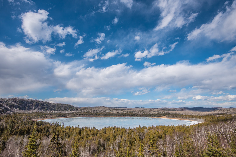 "THURSDAY, APRIL 9, 2015<br /> <br /> LAKES 3340<br /> <br /> ""Early Spring on Teal Lake""<br /> <br /> Any day now the ice should be starting to disappear over northern Minnesota lakes.  This photo of Teal Lake in Grand Portage, MN was taken on April 2nd, when the temperature got into the upper 50's.  Since then we have had a cool-down with our highs only getting into the mid to upper 30's.  On the 2nd, though, it was a very warm day and things were changing rapidly.  By the end of the day Teal Lake still had thick ice on it, but the surface of the ice was covered with giant melt puddles.  If you look closely at the lake in this photo you can see the blue sky and clouds reflected in the melt puddles. With temperatures expected to rise into the low 50's again this weekend, we should see some more melting going on!<br /> <br /> Camera: Nikon D750<br /> Lens: Nikon 16-35mm f/4<br /> Focal length: 18mm<br /> Shutter speed: 1/800<br /> Aperture: f/11<br /> ISO: 200"