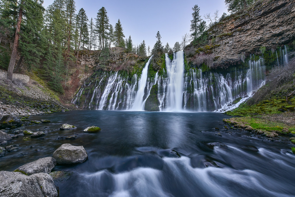 "WEDNESDAY, APRIL 1, 2015<br /> <br /> CALIFORNIA 2315<br /> <br /> ""Burney Falls""<br /> <br /> One of the coolest things we saw on our trip was Burney Falls in northern California.  What an amazing waterfall!  There are actually only a few channels of water that come all the way down from the top of the falls.  The rest of the water  runs through the rock and seeps out of the cliff face below the top of the falls.  The result is a very wide waterfall with countless streams of water that looks more like something you might see in Hawaii.  We timed our visit so we would be there in the evening without any direct light, that way I could use longer shutter speeds to blur the movement of the water.  <br /> <br /> Camera: Nikon D750<br /> Lens: Nikon 14-24mm f/2.8<br /> Focal length: 14mm<br /> Shutter speed: 1.3 seconds<br /> Aperture: f/16<br /> ISO: 200"