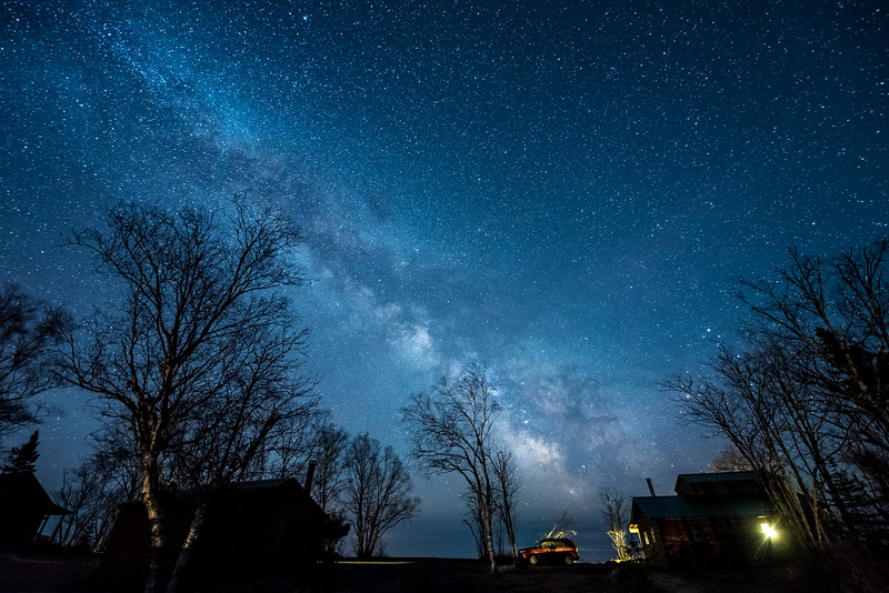 "MONDAY, APRIL 20, 2015<br /> <br /> MILKY WAY 4207<br /> <br /> ""Quiet Night at Hollow Rock Resort""<br /> <br /> If you want a beautiful and easy location to view the Milky Way Galaxy over Lake Superior, look no further than Hollow Rock Resort in Grand Portage, MN.  This sublime location on the shoreline of Lake Superior has comfortable cabins with superb views of Lake Superior and the Milky Way right outside your door.  Not to mention the famous Hollow Rock itself!  Last week I spent part of the night photographing the night sky at the resort.  I captured an incredible view of the galaxy over Hollow Rock (see my post from yesterday) as well as this view which shows a couple of the cabins and the trees that surround them.  Lake Superior is right on the other side of the car that you see in this photo.  Amazing views are always present at Hollow Rock Resort, but if you want to see the core of the Milky Way, now through summer is the time.  The core is not visible in our winter sky. And, as you can see from this photo, all you need to do is walk a few steps out in front of your cabin to see this unforgettable sky!<br /> <br /> For more information about Hollow Rock Resort click this link:<br /> <br /> <a href=""http://www.hollowrockresort.com/"">http://www.hollowrockresort.com/</a><br /> <br /> Camera: Nikon D750<br /> Lens: Nikon 14-24mm f/2.8<br /> Focal length: 14mm<br /> Shutter speed: 30 seconds<br /> Aperture: f/2.8<br /> ISO: 6400"