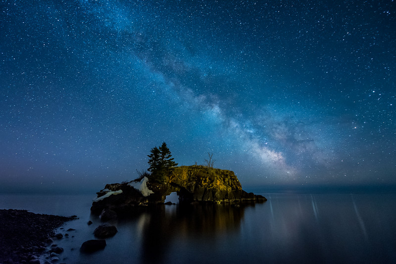 "SUNDAY, APRIL 19, 2015<br /> <br /> MILKY WAY 4213<br /> <br /> ""Hollow Rock Heaven""<br /> <br /> The Milky Way over Hollow Rock in Grand Portage, Minnesota.  I finally have a lens and a camera that is allowing me to capture the views of the night sky that I've always dreamed about.  Ever since I've been practicing photography (a little over 20 years now), I've been into low-light photography and photographs of the night sky in particular.  While I have always loved making images after dark, I've never been able to fully realize my vision due to limitations in my camera gear.  Don't get me wrong, I still love all those night images I've made over the years.  There will always be a place in my heart and my memory of all those experiences of making those images.  <br /> <br /> But, they were far from the quality of the images that I am now creating.  This photograph is a perfect case in point.  It looks like something from a dream.  The Milky Way is so vivid and clear, and seems to jump off the screen at you.  And, the noise performance is outstanding.  The photo has noise, to be sure (any photo at ISO 6400 is going to have noise) but the quality of the noise is unbelievable.  It actually reminds me of a really fine film grain.  I can't wait to make a big print out of this photograph.  I think it's going to be quite stunning!  I have never been more excited than I am now about making more images of the night sky :-)  <br /> <br /> FYI - The light on the rock is from an interior table lamp that was left on in one of the nearby cabins of Hollow Rock Resort.  It cast just enough light on the rock to give a nice soft level of illumination.  The white areas that you see on the left side of the rock are the last remnants of ice from the winter season.<br /> <br /> Oh, and just in case you're wondering about the equipment used to make this photograph, the camera used was a full-frame Nikon D750 with a Nikon 14-24mm f/2.8 lens.<br /> <br /> Camera: Nikon D750<br /> Lens: Nikon 14-24mm f/2.8<br /> Focal length: 14mm<br /> Shutter speed: 30 seconds<br /> Aperture: f/2.8<br /> ISO: 6400"
