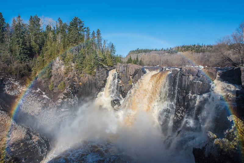 "FRIDAY, APRIL 17, 2015<br /> <br /> ONTARIO 3909<br /> <br /> ""Full Rainbow at High Falls""<br /> <br /> For one of my days off this week I started the morning off with a hike to High Falls on the Canadian side of the river, in Pigeon River Provincial Park.  Regular followers of my photography know that I often photograph the falls from the U.S. side, but it's been quite a long time since I've photographed it from the Canadian side.  Since the river opened up just about a week ago I figured it was a good time to make the venture to the other side.  <br /> <br /> It was a very difficult prospect getting this shot.  The temperature had dipped down below freezing overnight and with the water level at the falls being quite high, all the spray was blowing right up into the overlook area and freezing into a layer of ice on everything.  The ground, rocks, trees and railings were all coated in ice.  On the U.S. side this wouldn't be much of a problem as there is a nice level boardwalk to walk on.  On the Canadian side, however, it's just bare ground and that ground is anything but flat.  <br /> <br /> It was quite an adventure staying upright while trying to get to the railing and the view of the falls.  And, once I got there, it took several attempts before I got a shot where the lens wasn't completely covered in freezing water droplets.  In between shots I would have to turn around, putting my back to the spray and wipe the lens clean.  Then I would cover the lens with my hand, turn back around and try to get just one shot before the water hit the lens again.  The water coated the lens pretty much instantly once I pulled my hand away.  I think it took at least 20 attempts before I got a reasonably clean image.  This one still had a few water droplets on it, but I was able to use the healing brush in Lightroom to remove the spots.  As usual, all of that effort was worth it and I came away with a great shot of the falls and the full rainbow in front of it.  Time well spent, I'd say!<br /> <br /> Camera: Nikon D750<br /> Lens: Nikon 14-24mm f/2.8<br /> Focal length: 18mm<br /> Shutter speed: 1/800<br /> Aperture: f/11<br /> ISO: 400"