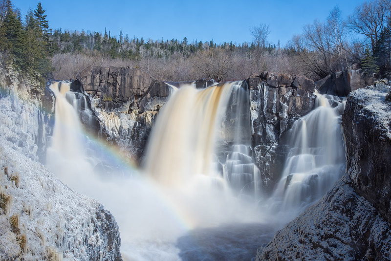 "FRIDAY, APRIL 24, 2015<br /> <br /> PIGEON RIVER 4332<br /> <br /> ""Spring Ice and Rainbow at High Falls""<br /> <br /> It's that glorious time of year for waterfall watching along the north shore of Lake Superior!  Especially at High Falls in Grand Portage State Park, arguably one of the most beautiful waterfalls in the state of Minnesota (not to mention the tallest!).  This photo was taken yesterday morning after a stretch of several cold days where the high temperature was in the mid to upper 30's.  The colder temps meant that at night the spray from the waterfall was freezing to everything that it landed on, coating everything along the gorge walls in a thick layer of ice.  It makes for a beautiful scene on a sunny morning thanks to the added effect of a rainbow!  I used a 6-stop neutral-density filter to slow down the exposure to 2 seconds and blur the movement of the water.  The forecast is looking pretty nice for the weekend so better head up the shore and check out the waterfalls!<br /> <br /> Camera: Nikon D750<br /> Lens: Nikon 24-120mm f/4<br /> Focal length: 48mm<br /> Shutter speed: 2 seconds<br /> Aperture: f/22<br /> ISO: 100"