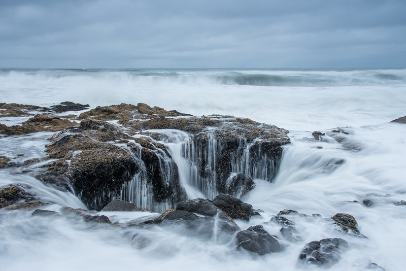 "SATURDAY, APRIL 4, 2015<br /> <br /> OREGON 3074<br /> <br /> ""Thor's Well""<br /> <br /> One of the features I really wanted to see along the Oregon coast was Thor's Well, part of the Cape Perpetua Scenic Area.  Thor's Well is a salt water fountain driven by the power of the ocean tide.  The height of the tide and the direction of the ocean swells both contribute to the fascinating behavior of the well.  The phenomena is best experienced from about an hour before high tide to an hour after.  This is when you will see the most water rising up from the well then running back down into it.  High tide is also the most dangerous time to be there, as you could easily get swept into the well if you're not careful or not paying attention to the waves.  <br /> <br /> It certainly is one of the most fascinating natural features to see along the Oregon coast.  I was hoping for some beautiful sunset clouds and colors to photograph with the well in the foreground.  However, the first afternoon we went there it was completely cloudy and raining constantly.  The next day looked more promising, as the sky was party sunny for most of the day.  By the time sunset rolled around, however, the clouds had moved back in and it actually started pouring again while I was photographing the well.  Those two days were the only chance I had to photograph the well as we had to head back to Las Vegas the next day to catch our flight home.  Oh well, something to look forward to on our next trip to the coast.  Maybe conditions will be more favorable and I'll catch an awesome sunset over the well :-)<br /> <br /> Camera: Nikon D750<br /> Lens: Nikon 24-120mm f/4<br /> Focal length: 32mm<br /> Shutter speed: 1 second<br /> Aperture: f/22<br /> ISO: 100"