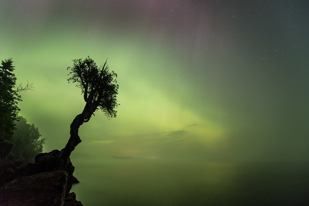 "SUNDAY, AUGUST 16, 2015<br /> <br /> AURORA 8761<br /> <br /> ""Lake Superior Fog and the Northern Lights""<br /> <br /> Last night was another first in photography for me: photographing the northern lights AND Lake Superior fog at the same time!  While we were sitting down along the shoreline last night watching the lights dance overhead some fog moved in and filled the bay.  It reduced the intensity of the lights somewhat but it also changed the quality of the light that we were seeing.  It made for an interesting look in the photos.<br /> <br /> Camera: Nikon D750<br /> Lens: Nikon 14-24mm f/2.8<br /> Focal length: 14mm<br /> Shutter speed: 20 seconds<br /> Aperture: f/2.8<br /> ISO: 1250"