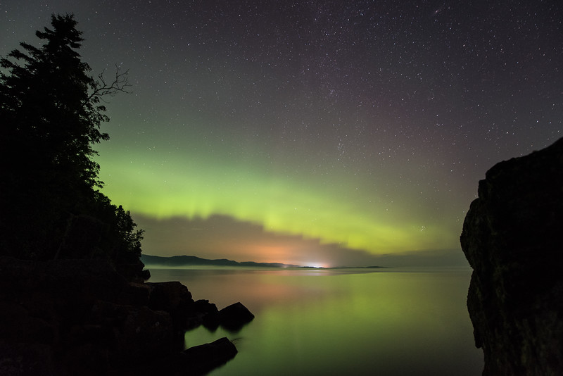 "SUNDAY, AUGUST 16, 2015<br /> <br /> AURORA 8732<br /> <br /> ""Wauswaugoning Glow""<br /> <br /> Early on in last night's aurora borealis display along the shoreline of Wauswaugoning Bay in Grand Portage, MN.  For the first 45 minutes or so this glowing ribbon of aurora entertained us from the northern horizon. As midnight approached the lights did pick up in their intensity but it was nice enjoying this early soft glow as well.<br /> <br /> Camera: Nikon D750<br /> Lens: Nikon 14-24mm f/2.8<br /> Focal length: 14mm<br /> Shutter speed: 30 seconds<br /> Aperture: f/2.8<br /> ISO: 1600"
