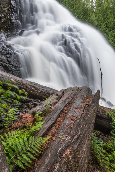 "SATURDAY, AUGUST 15, 2015<br /> <br /> PIGEON RIVER 8272<br /> <br /> ""Logging Remnants?""<br /> <br /> Some old-growth timber logs at the base of a waterfall in northeast Minnesota.  Possibly remnants from the days when logging was running rampant along the north shore, these logs have been laying here for as long as I can remember.  Perhaps they aren't from the days when most of the big timber in this area was logged, but I like to imagine that they are.  It's strange too that there are two sticks stuck in the rocks at the base of the falls (one of them is really obvious, the other less so as it is kind of behind the water).  I've never seen anything stuck in the rocks like that before at this waterfall.  Rather interesting, I think.<br /> <br /> Camera: Nikon D750<br /> Lens: Nikon 16-35mm f/4<br /> Focal length: 16mm<br /> Shutter speed: 3 seconds<br /> Aperture: f/11<br /> ISO: 200"